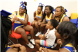 Cheerleaders Reading to Child